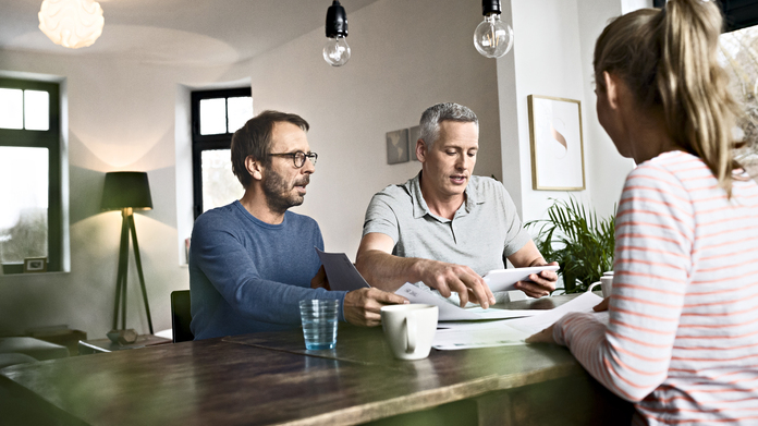A Vaillant expert giving product information to a couple, while sitting at the table